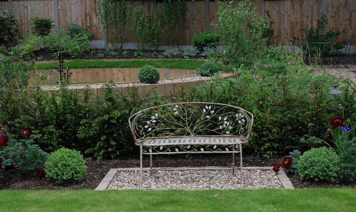 Decorative garden bench surrounded by planting