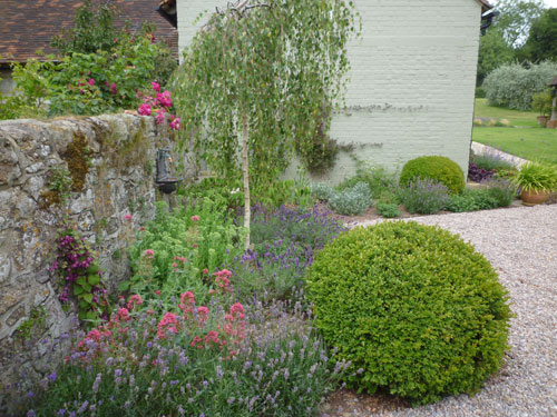 Converted farm courtyard garden by London garden designer Claudia de Yong